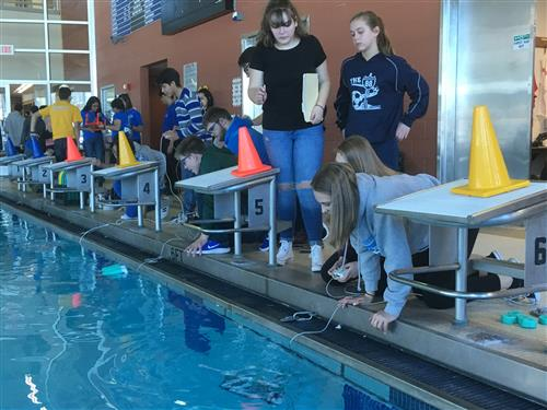 Students operate robots in a pool