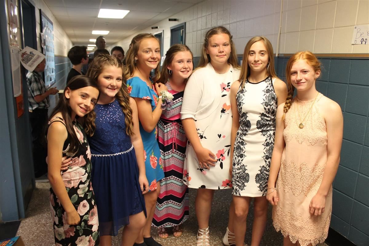 A group of girls dressed up for a ceremony.