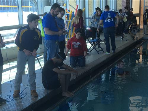 Students operate robots at the edge of an indoor pool