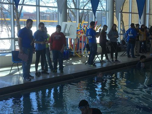 Students near a pool, controlling underwater robots
