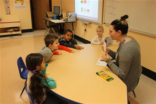 PreK students work with their teacher